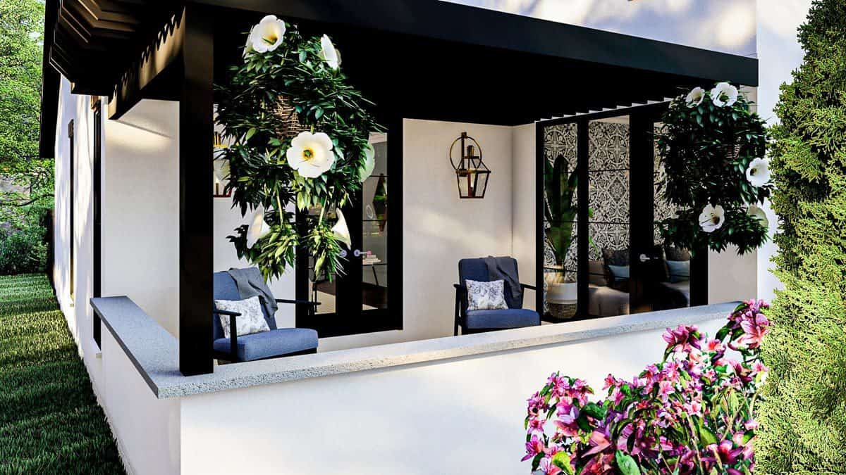 The covered porch is filled with cushioned armchairs, hanging plants, and lantern sconces.