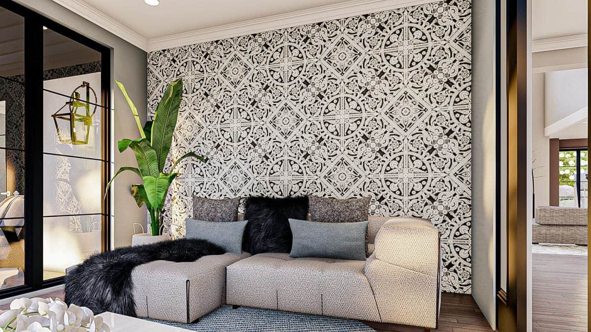 Sitting area with patterned wallpaper, a tall potted plant, and an L-shaped sofa topped with neutral and furry pillows.