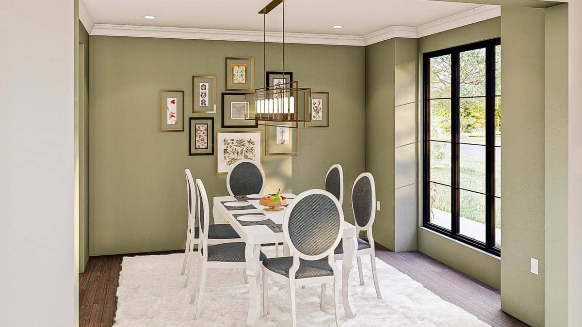 The formal dining room has round back chairs, a white rectangular table, a linear chandelier, and framed artworks adorning the sage green wall.