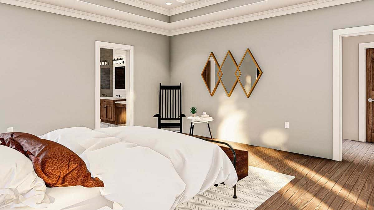 Primary bedroom with a tray ceiling, diamond-shaped mirrors. black rocking chair, and a cozy bed.