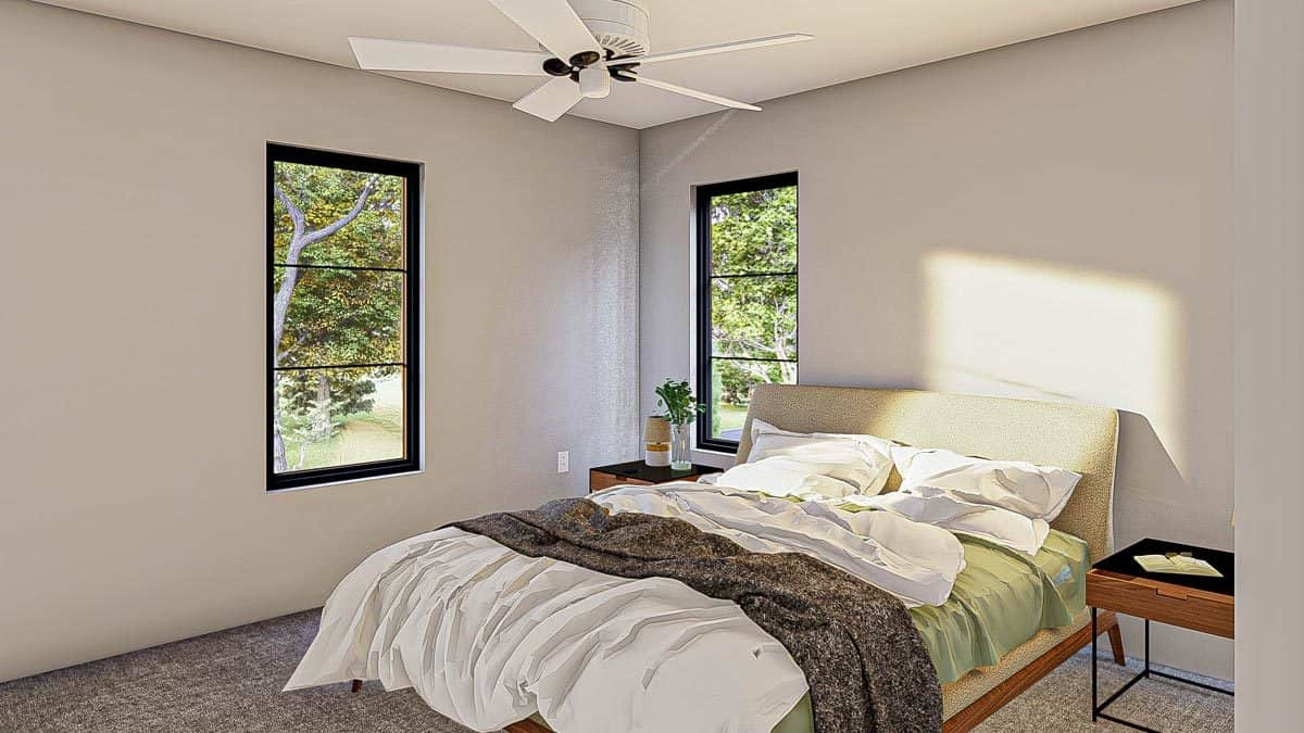 This bedroom offers a white ceiling fan and a beige upholstered bed flanked by iron nightstands.