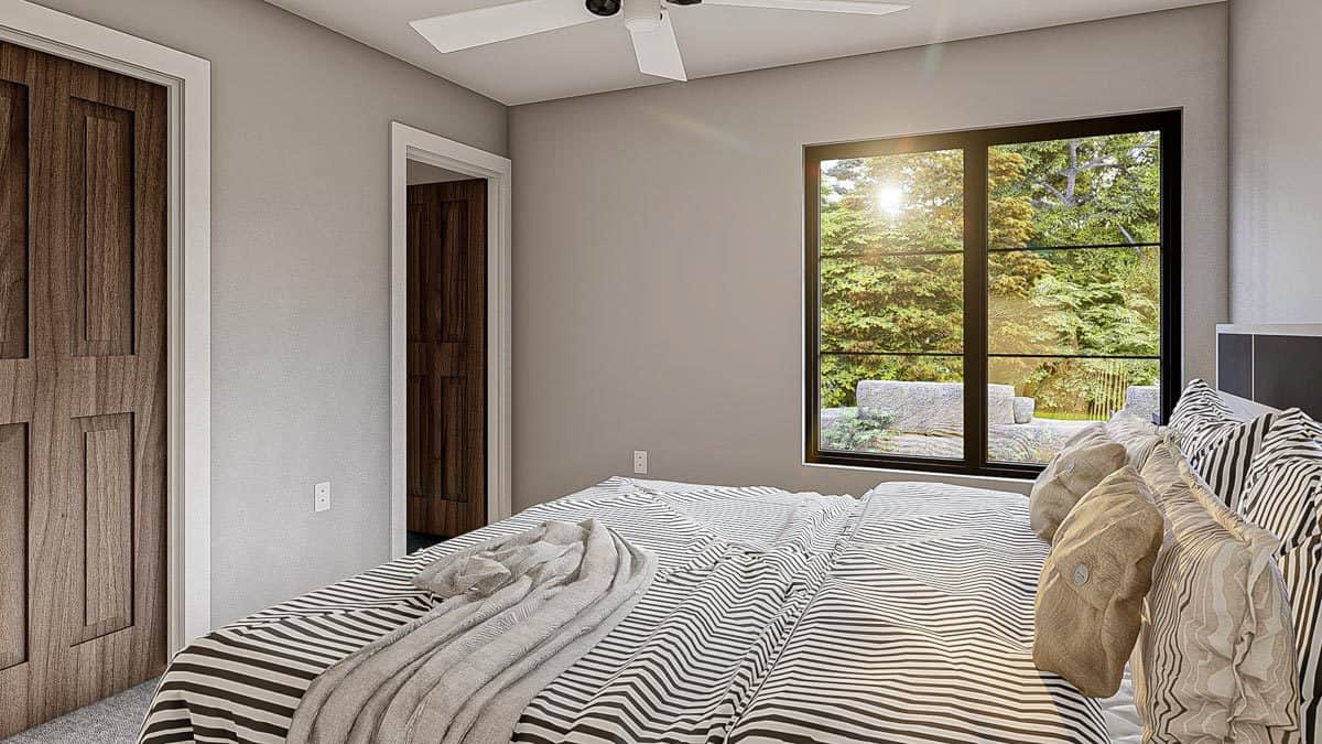 Bedroom with wooden doors, black aluminum-framed window, and a cozy bed dressed in striped bedding.