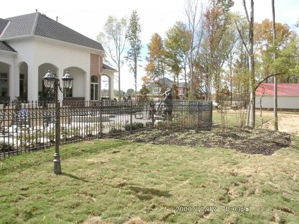 Rear exterior view showing the expansive lawn and wrought iron fence surrounding the house.