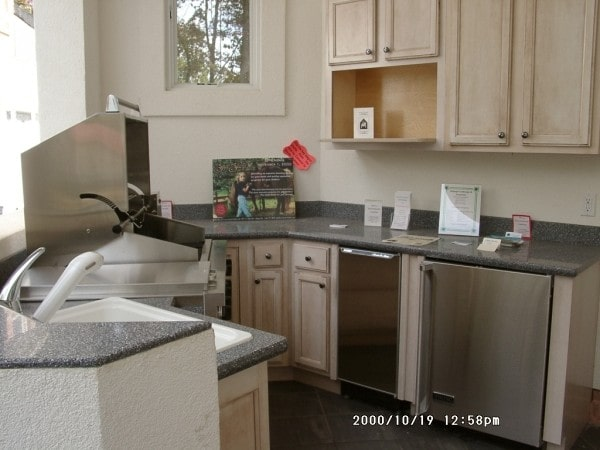 The summer kitchen is equipped with stainless steel appliances, black granite countertops, light wood cabinets, and a two-tier peninsula.