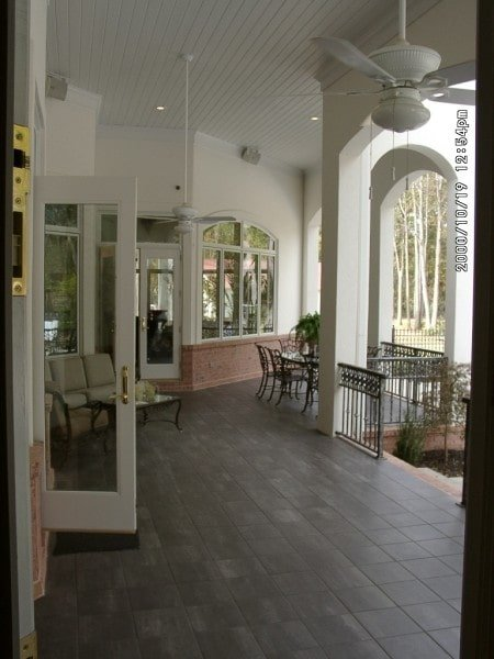 The covered porch has tiled flooring, white paneled ceiling, and multiple sitting areas.
