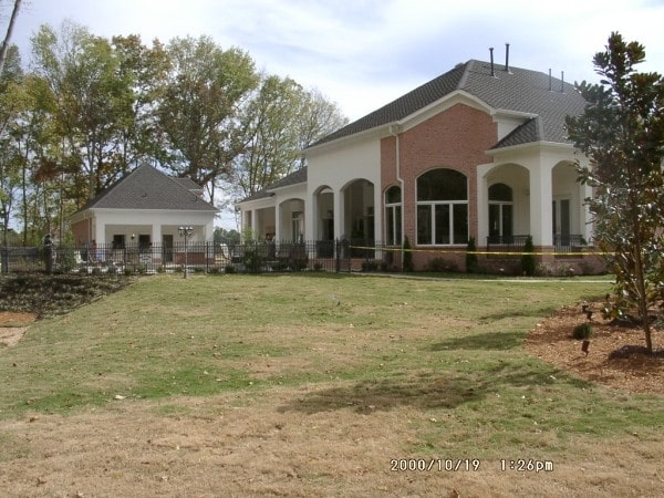 View of the house from the backyard showcasing its hipped rooflines and decorative open arches.