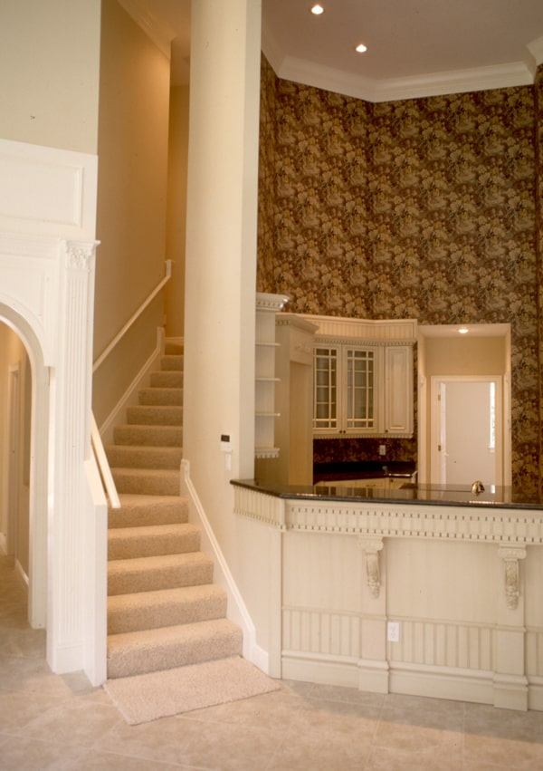 Carpeted staircase situated next to the wet bar that's accentuated with a classic wallpaper.