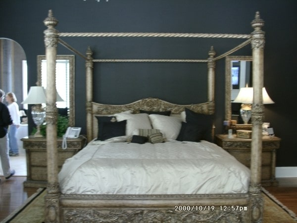 Matching nightstands with table lamps flank the carved wood canopy bed.