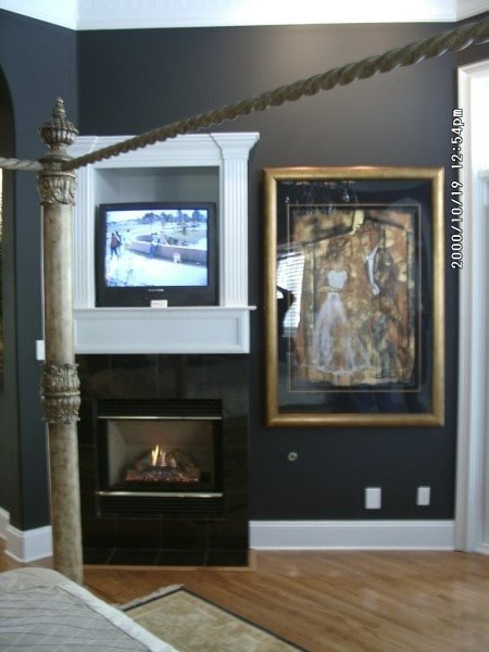 Glass-enclosed fireplace and a TV complete the primary bedroom.