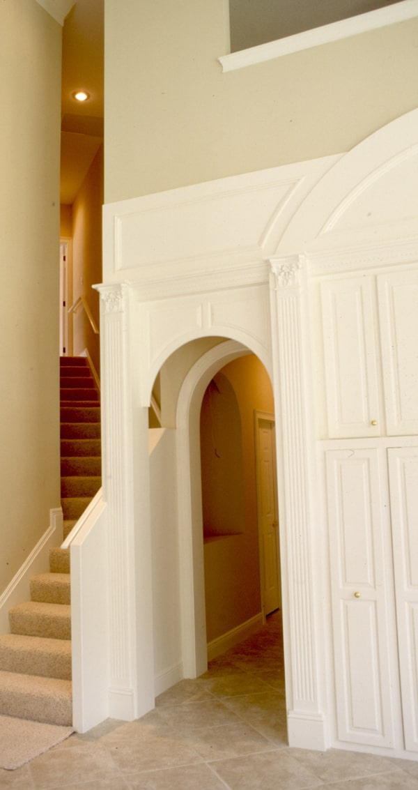 An arched hallway sitting beside the staircase leads to the family bedrooms.