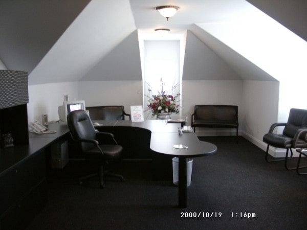Study with vaulted ceiling, black leather chairs, and a bespoke desk.