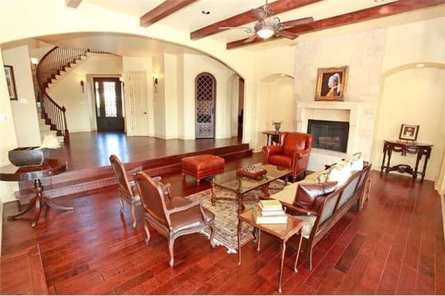 Opposite view of the living room showing the spacious foyer and a wine cellar enclosed in an arched door.