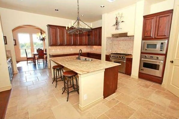 The kitchen has wooden cabinetry, stainless steel appliances, and a breakfast island.