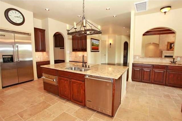 Wrought iron chandelier along with recessed ceiling lights illuminate the kitchen.