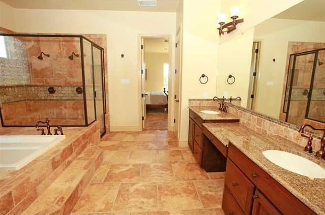 The primary bathroom is equipped with a dual sink vanity, a walk-in shower, and a deep soaking tub.