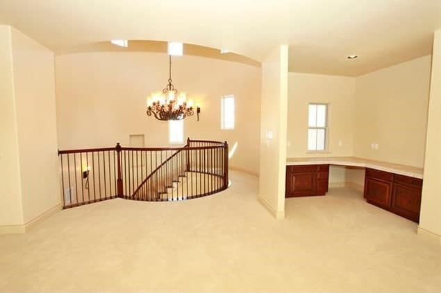 The spiral staircase leads to a spacious game room with carpet flooring and a granite top counter.