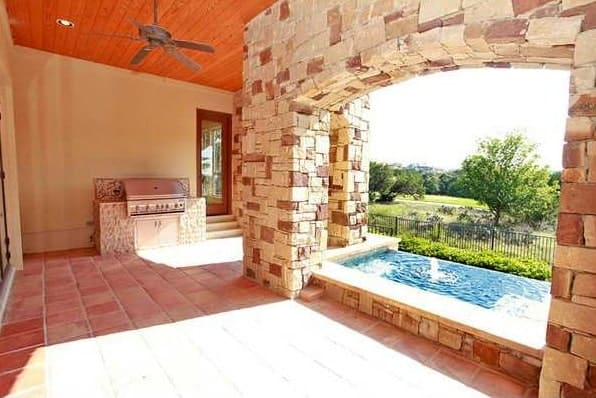 The covered porch is filled with a summer kitchen and a sparkling infinity pool.