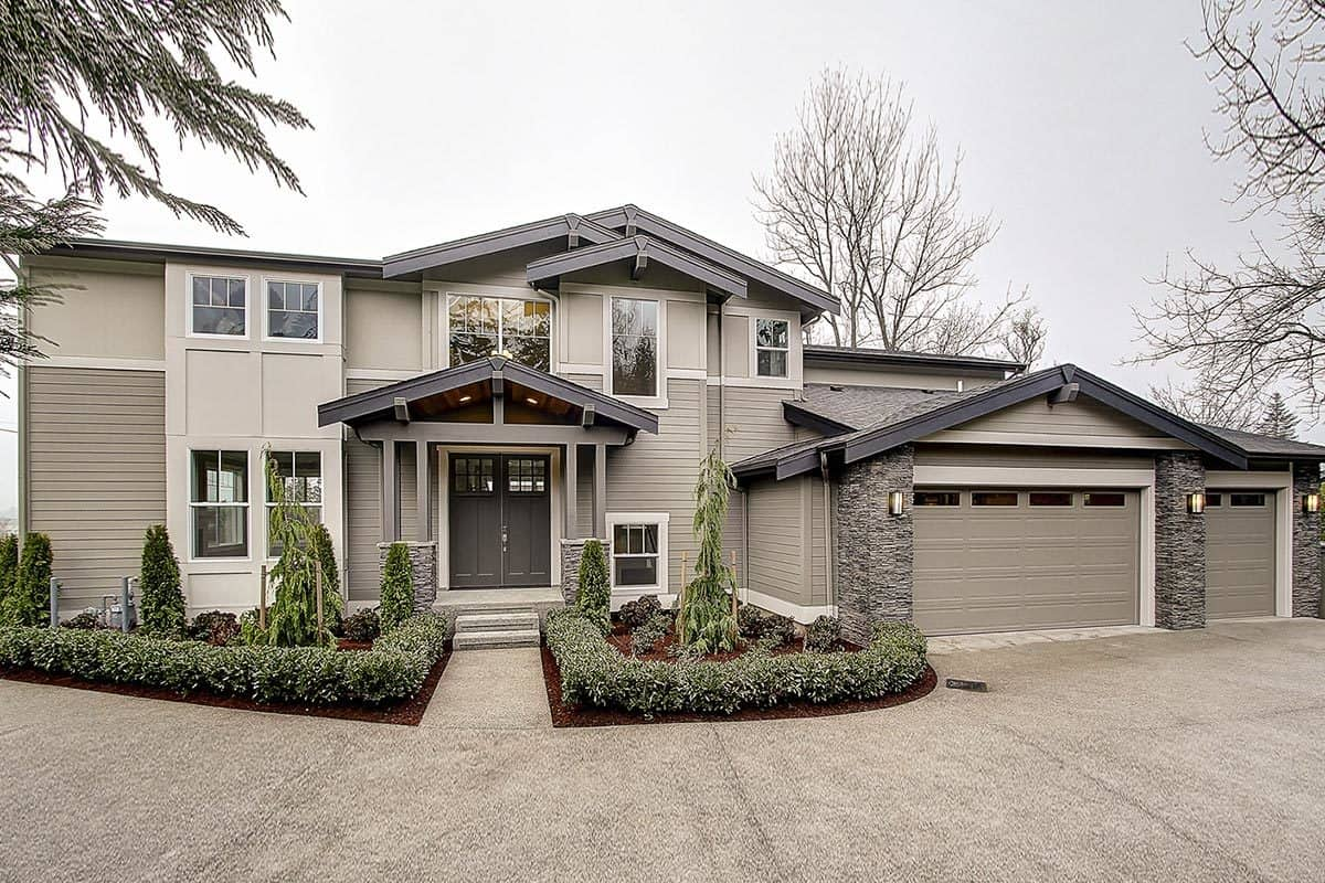 A blend of gray stucco and horizontal siding lend a contemporary charm to this Northwest home. Gable rooflines adorned with decorative brackets along with a portico lined with double columns complete the look.