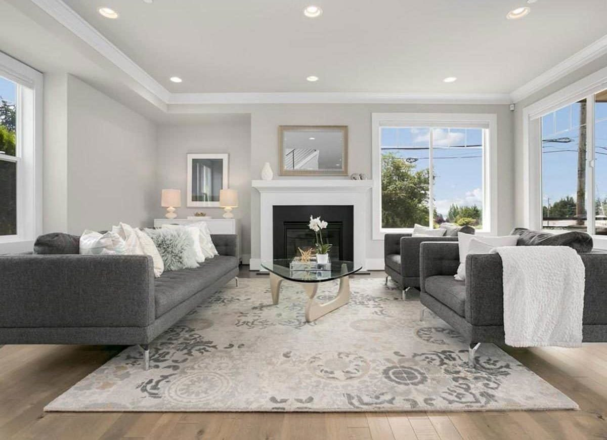 The living room has gray tufted seats, a sleek fireplace, and a glass top coffee table sitting on a printed area rug.