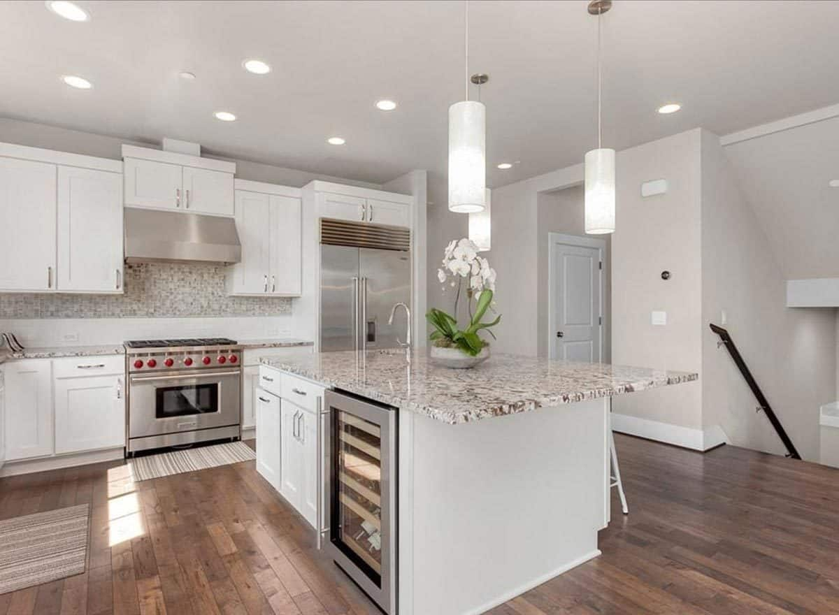 The kitchen island is fitted with a sink, built-in cabinets, and a beverage fridge.