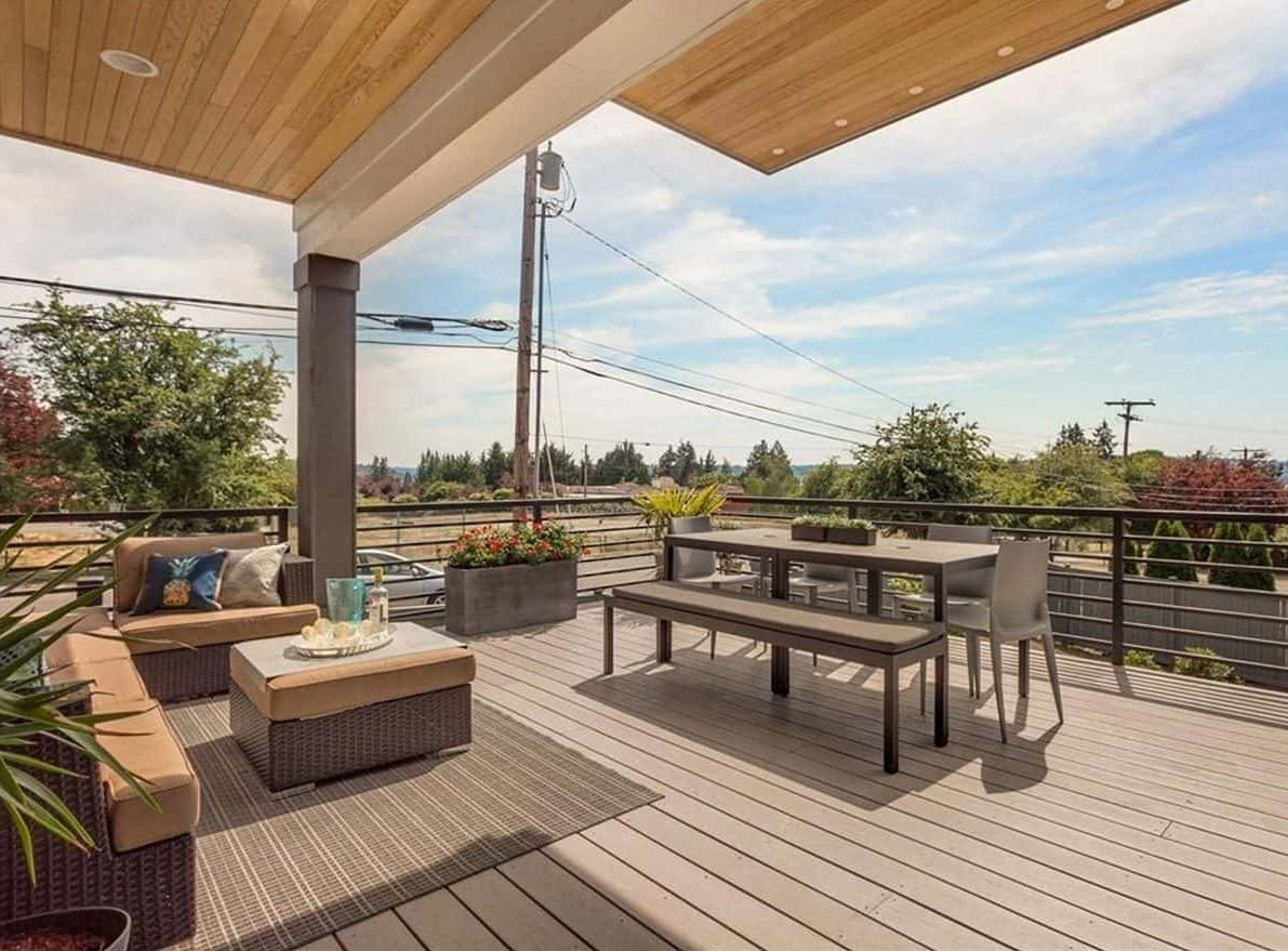 Covered deck with wicker seats, a rectangular dining set, striped rug, and concrete planters.