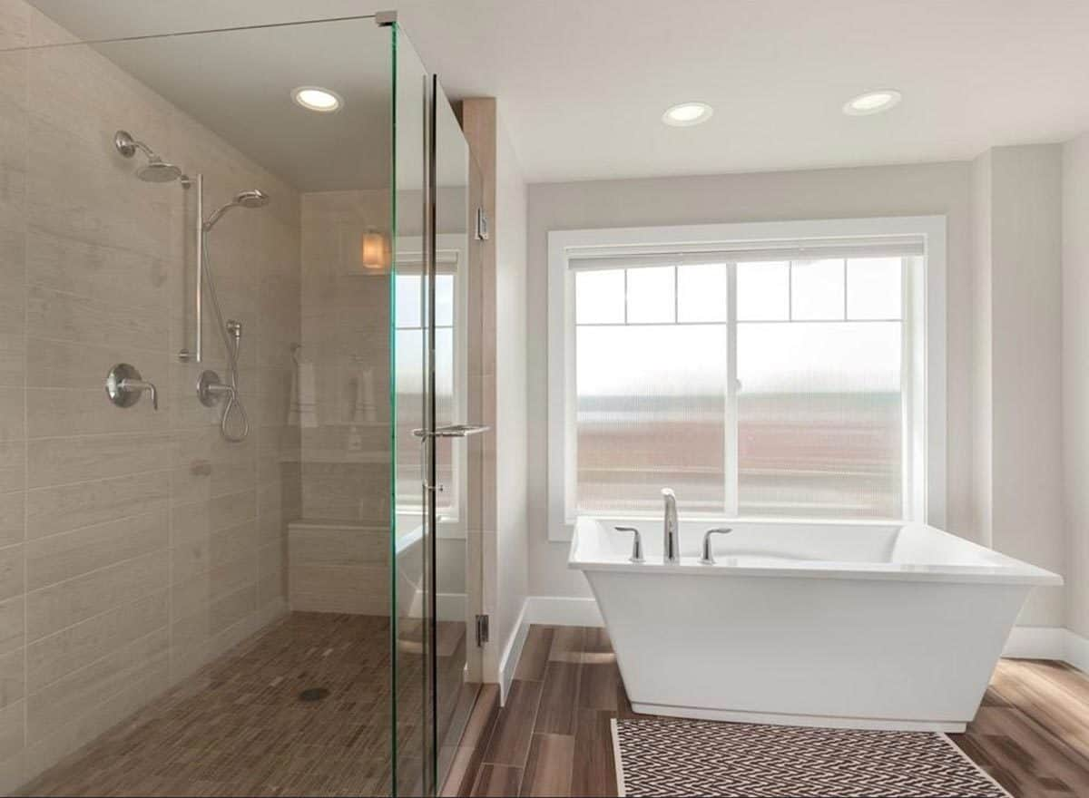 The primary bathroom is equipped with a walk-in shower and a freestanding tub complemented with a patterned rug.