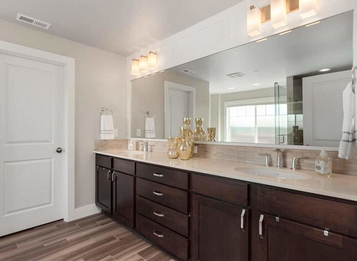Dual sink vanity with dark wood cabinets, long frameless mirror, and glass sconces.