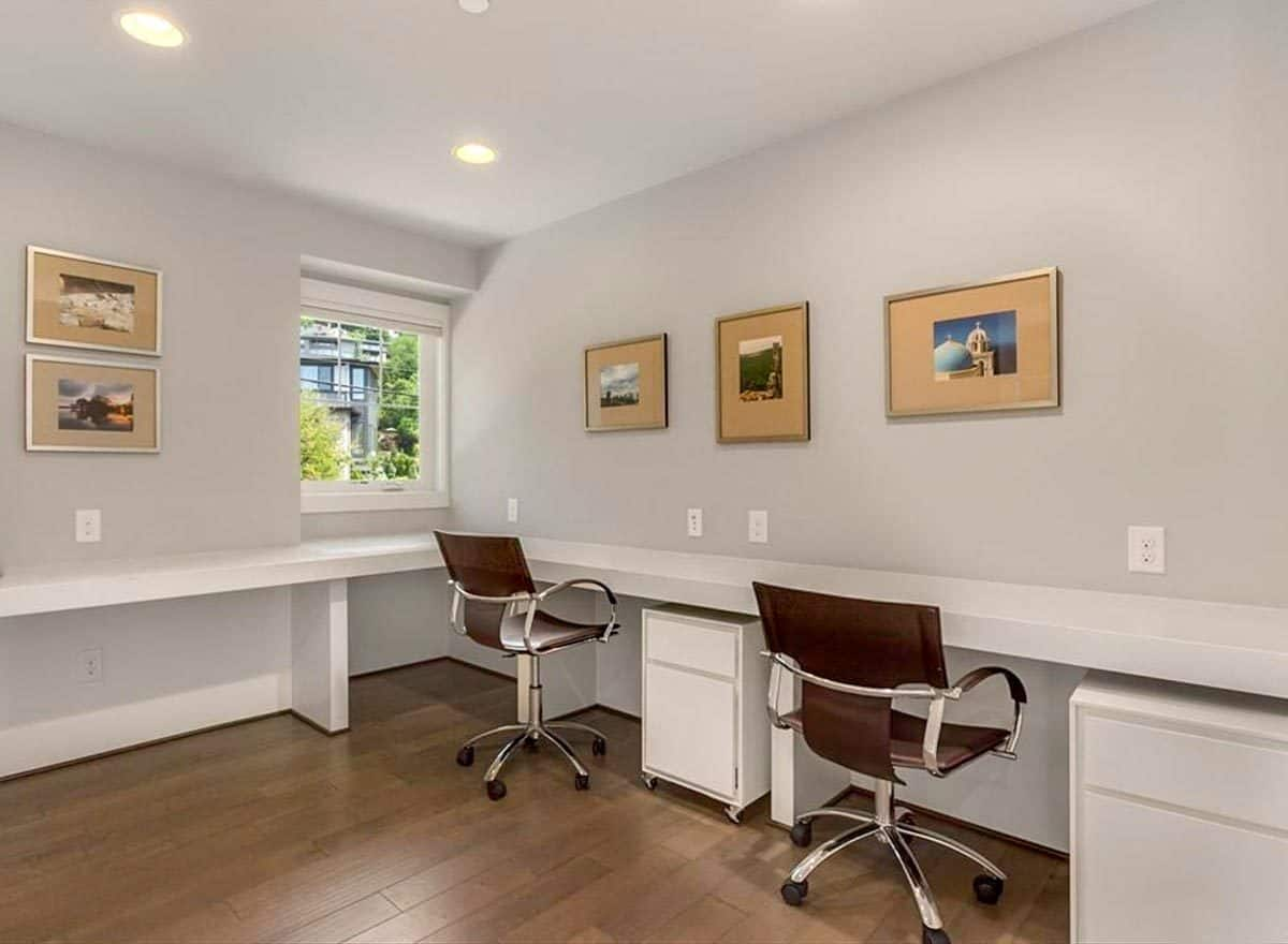 Study with swivel armchairs, built-in desk, and framed artworks adorning the gray walls.