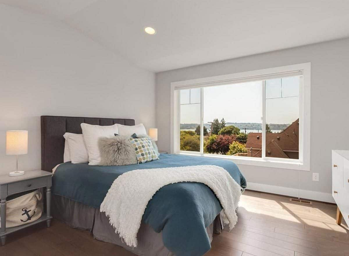 Bedroom with hardwood flooring, gray nightstands, and a wide window overlooking a breathtaking lake view.