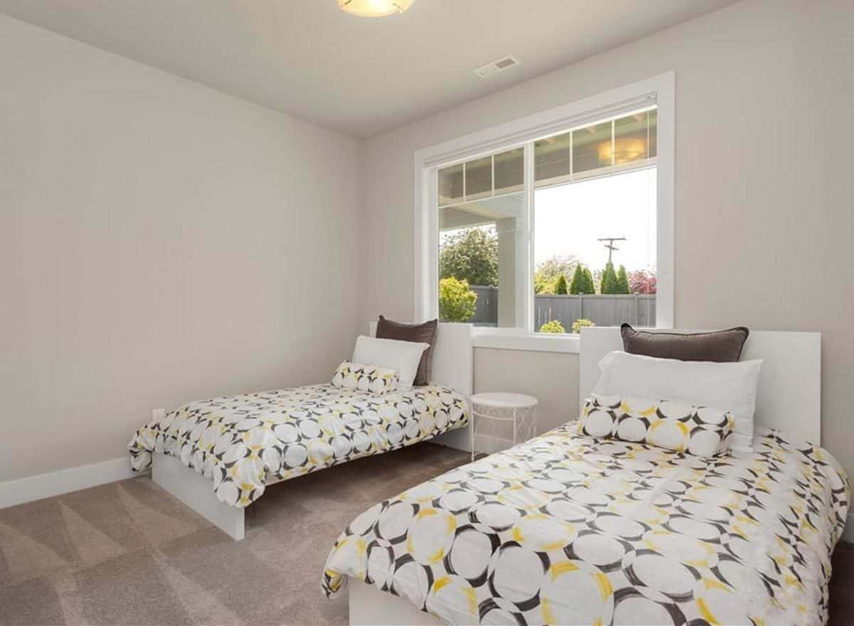 Guest bedroom with carpet flooring, white-framed windows, and two beds flanking a round nightstand.