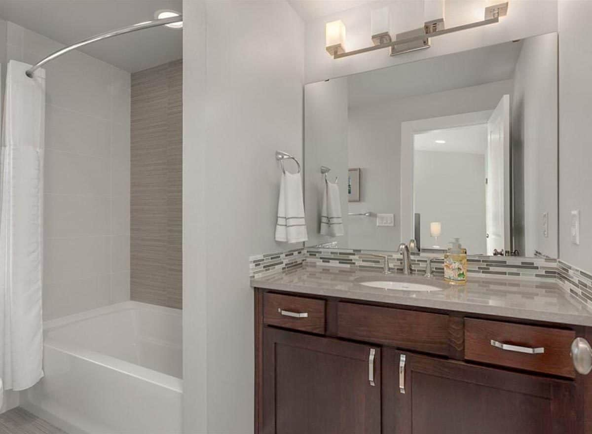Another bathroom with wooden vanity and a tub and shower combo enclosed in a white curtain.