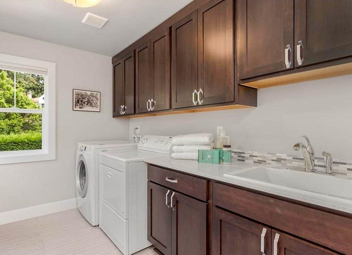 The utility room has dark wood cabinets, white appliances, a linear mosaic tile backsplash, and a porcelain sink.