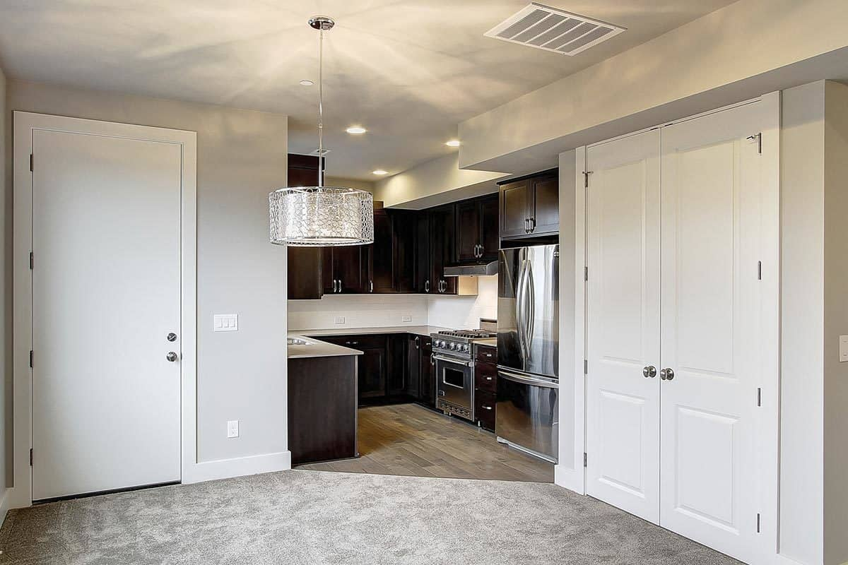 Kitchenette with dark natural wood cabinetry, stainless steel appliances, and granite countertops.