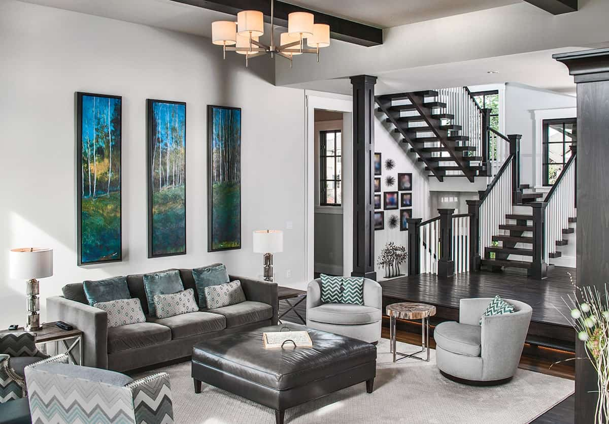 The living room has velvet seats, a leather ottoman, and multi-panel artwork adorning the gray wall.