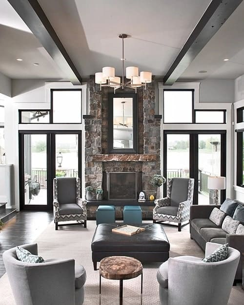 Stone fireplace and a contemporary chandelier hanging from the beamed ceiling complete the living room.