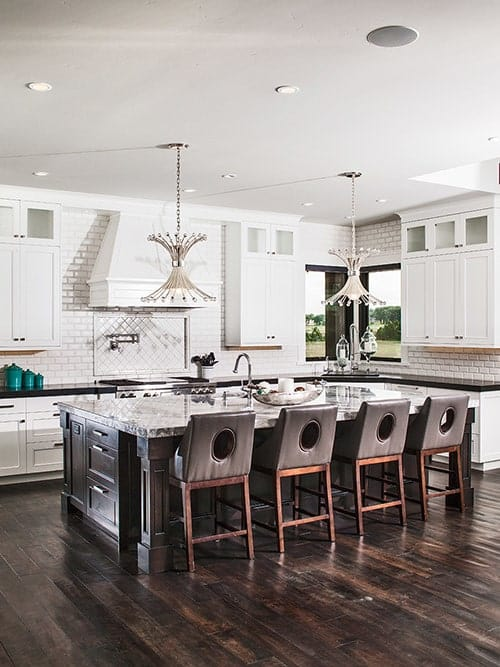 Kitchen with white cabinetry, subway tile backsplash, unique pendants, and a large breakfast island.