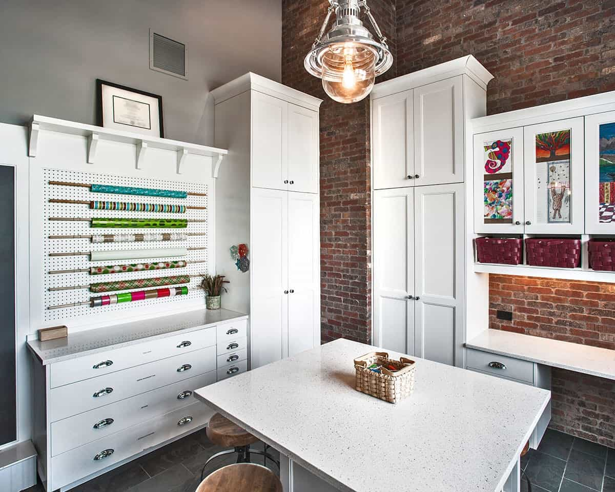 Craft room with white cabinets, a granite top island, bold storage baskets, and red brick accent wall.