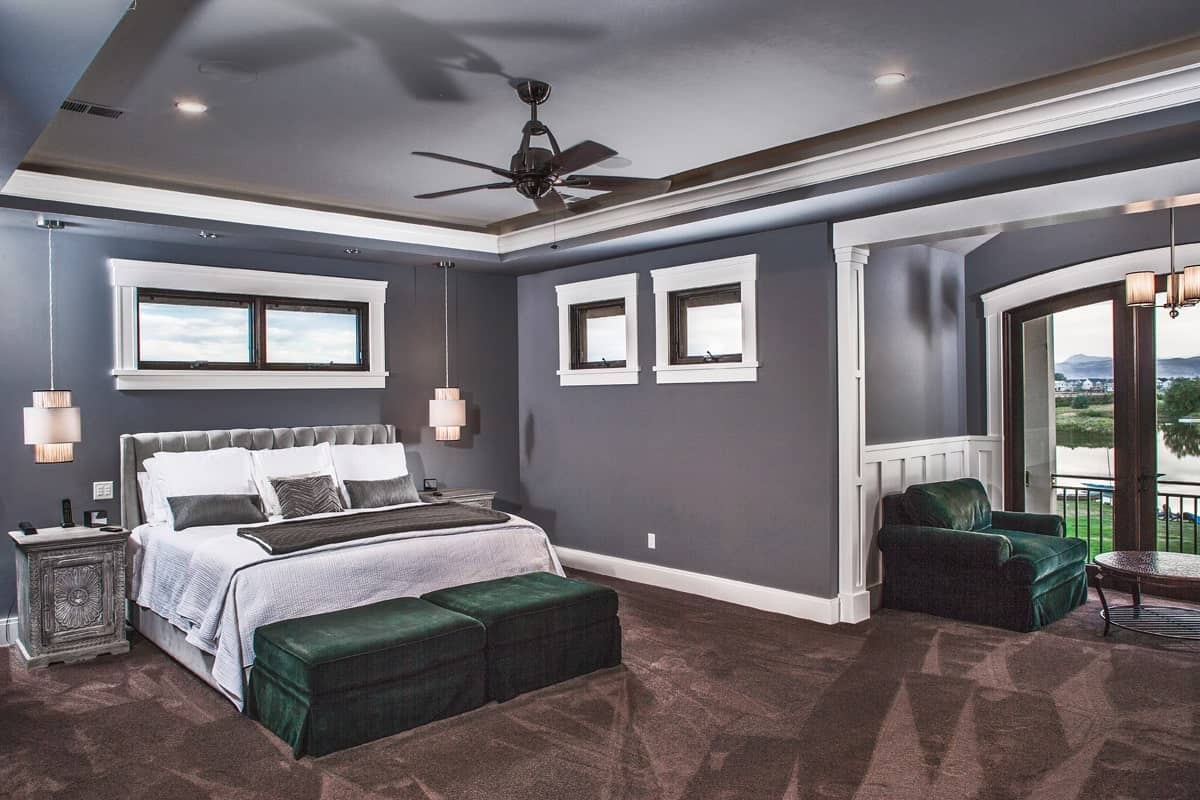 Primary bedroom with tray ceiling, carpet flooring, and a spacious sitting area that opens to a private balcony.