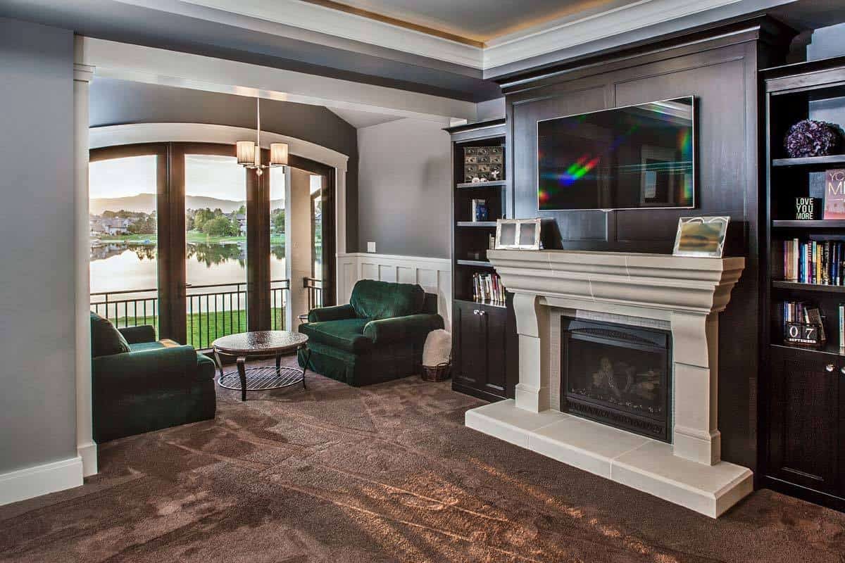 The sitting area is filled with a fireplace, wooden built-ins, and emerald green chairs paired with a round coffee table.