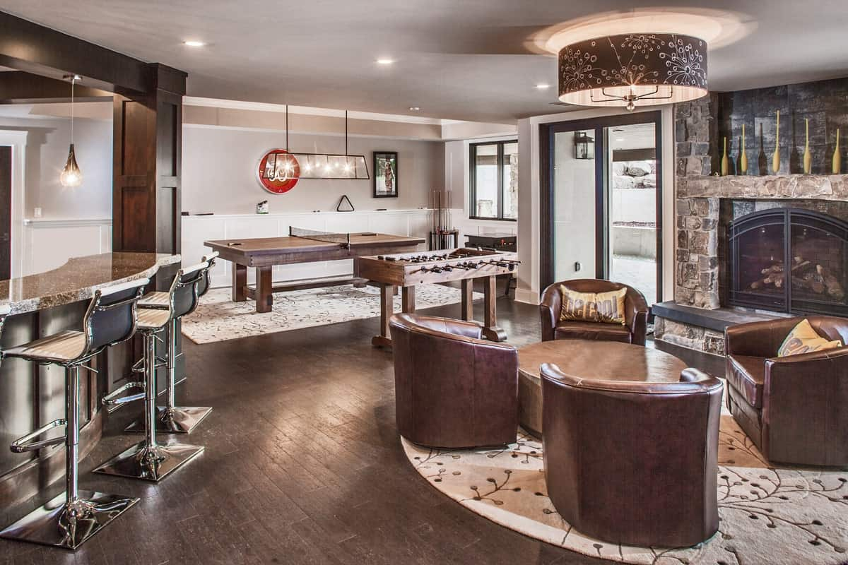 Recreation room with various game tables, round leather chairs, a stone fireplace, and a wet bar.