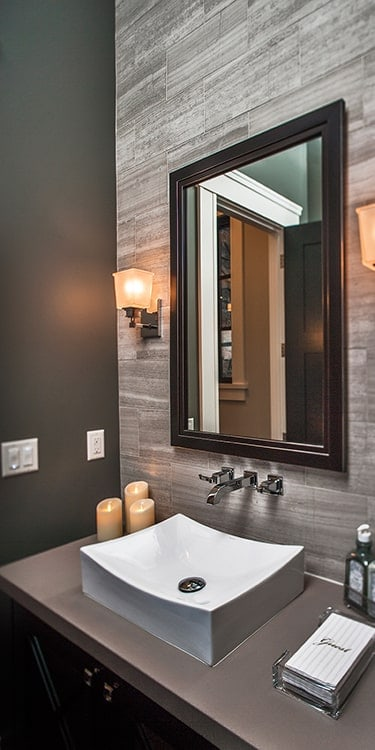 The powder room has a dark wood vanity that's topped with a vessel sink and wooden framed mirror.