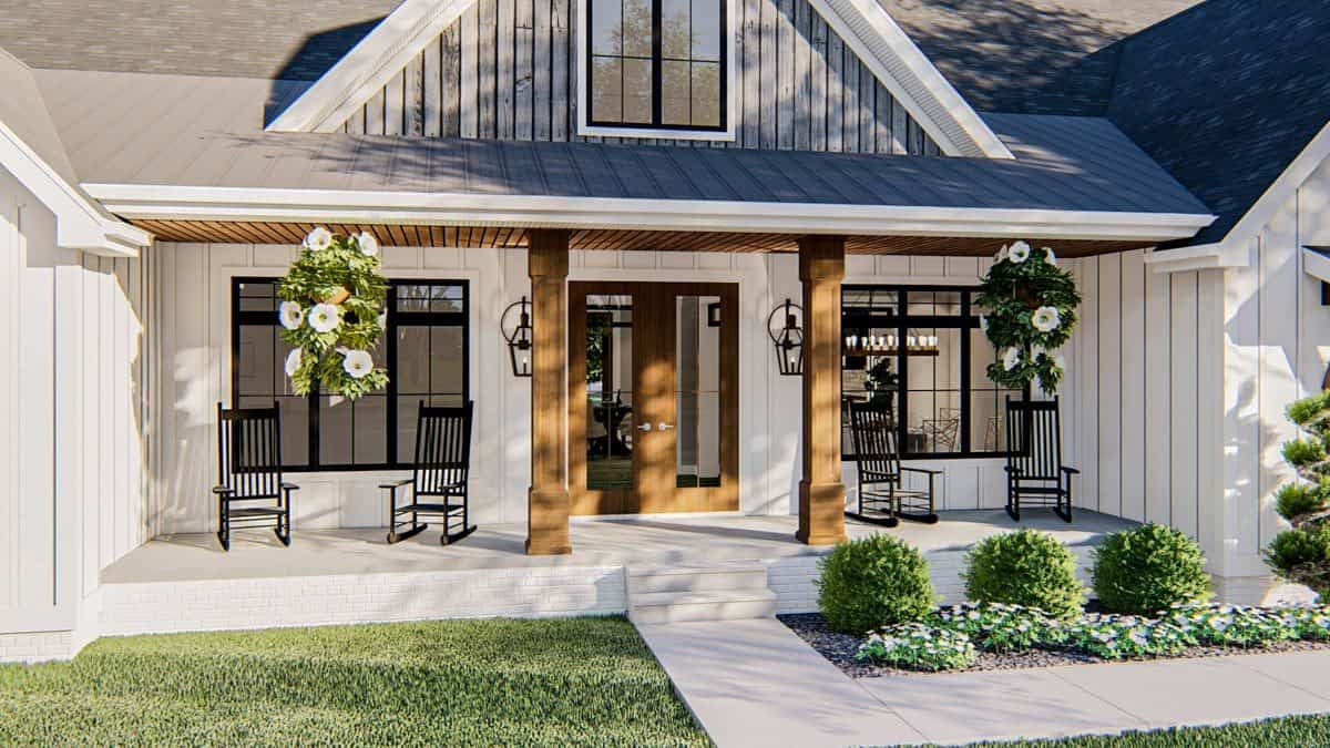 The front covered porch is filled with dark wood rocking chairs and fresh hanging plants.
