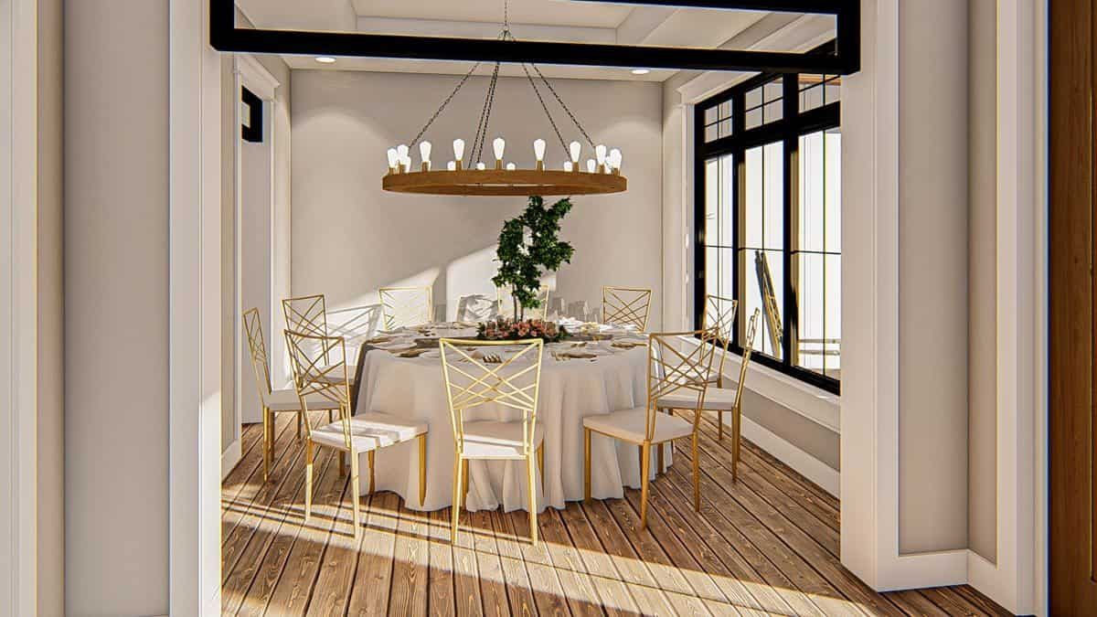 Formal dining room with white cushioned chairs, a round dining table, and an oversized chandelier.