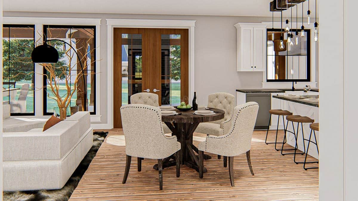 Breakfast area with a round dining table and beige tufted chairs. It sits in between the kitchen and living room.