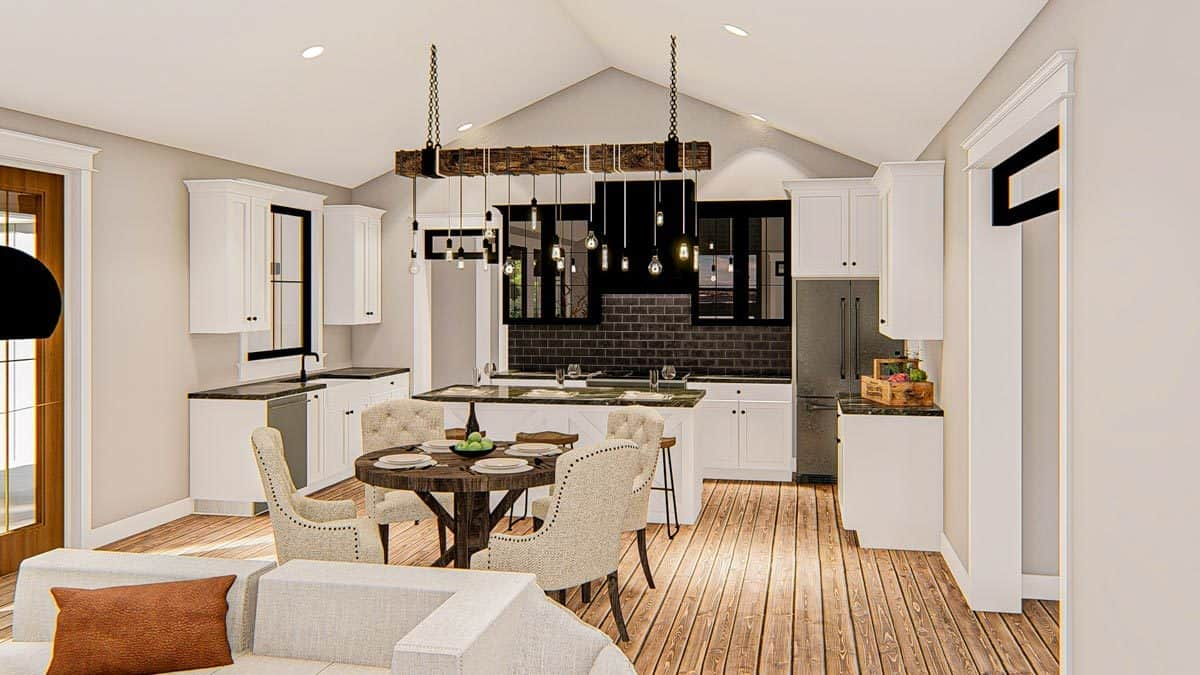 The kitchen at the far end is equipped with slate appliances, granite countertops, black subway tile backsplash, and a center island lit by bulb pendants hanging from the rustic beam.