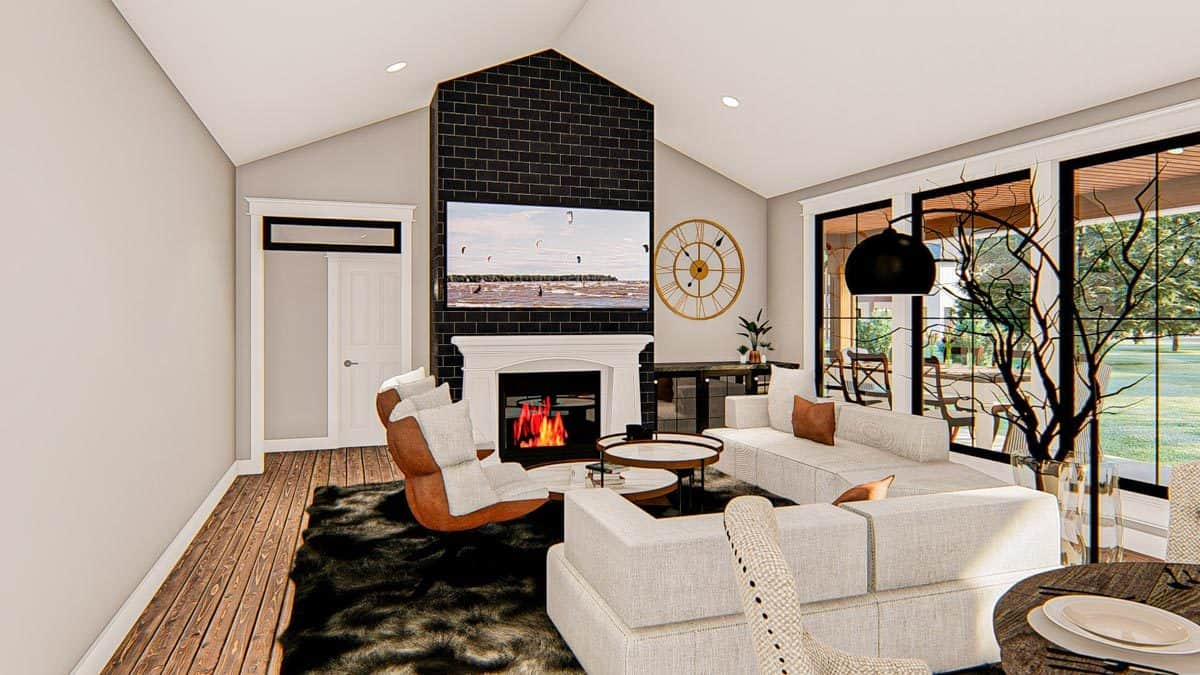 Living room with light gray sectionals, cushioned chairs, a modular coffee table, and a fireplace with a TV on top.