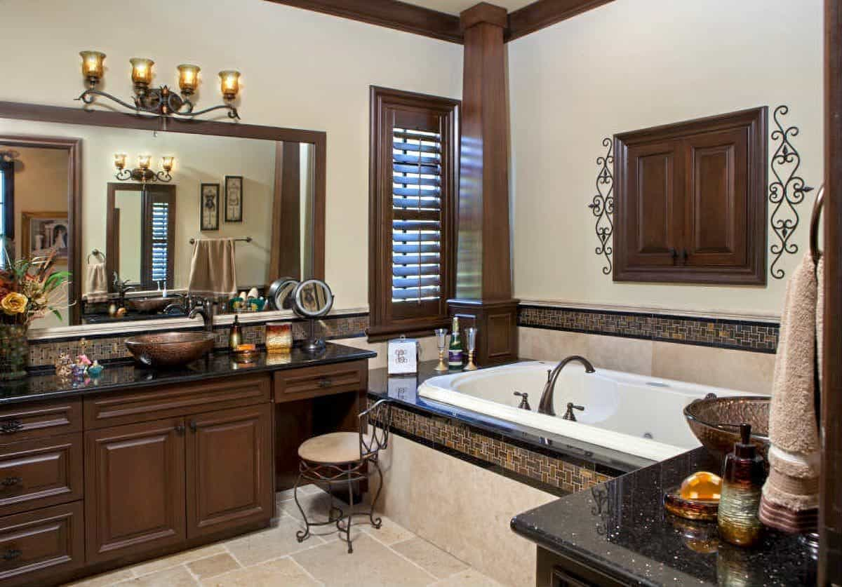 Primary bathroom with a deep soaking tub and separate his and her vanities topped with vessel sinks.