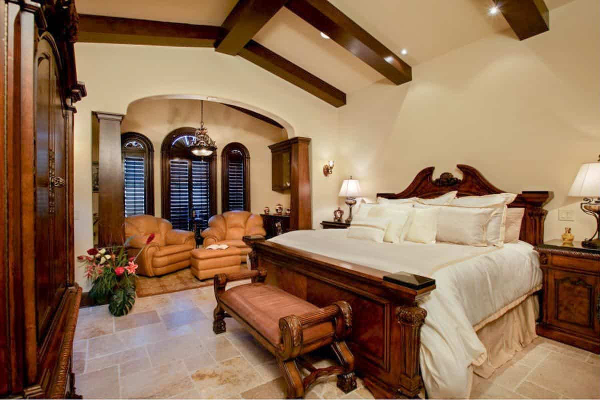 The primary bedroom has wooden furnishings, a beamed ceiling, and a sitting area filled with leather seats.
