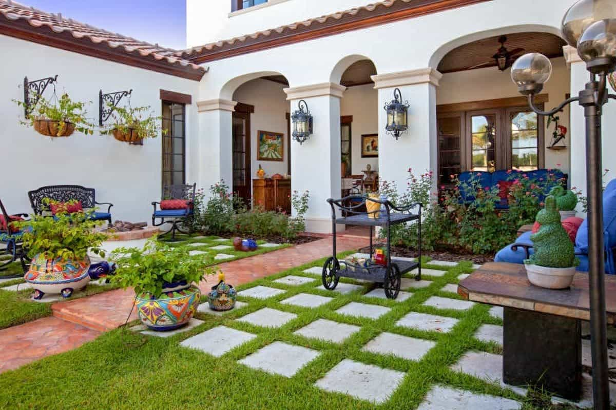Courtyard with multiple sitting areas and lush green lawn topped with concrete stones.