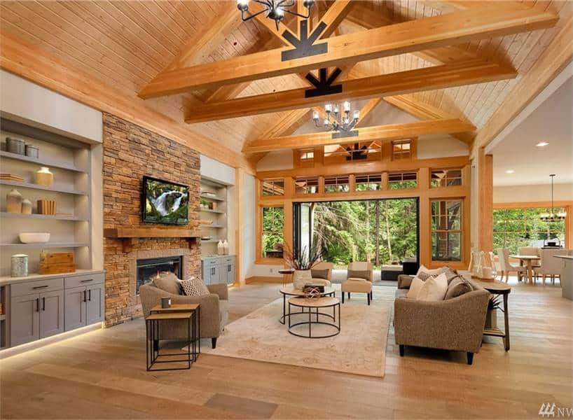 Living room with beige seats, modular tables, gray built-ins, a stone fireplace, and a cathedral ceiling with exposed wood beams.